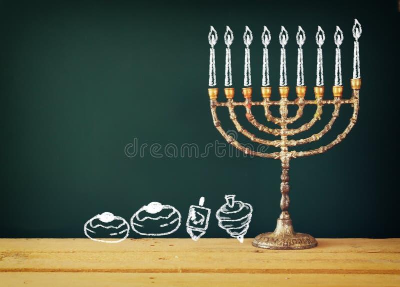 Beeld van Joodse vakantiechanoeka met tekenings menorah kaarsen (traditionele Kandelabers), donuts en dreidels (tol) stock foto