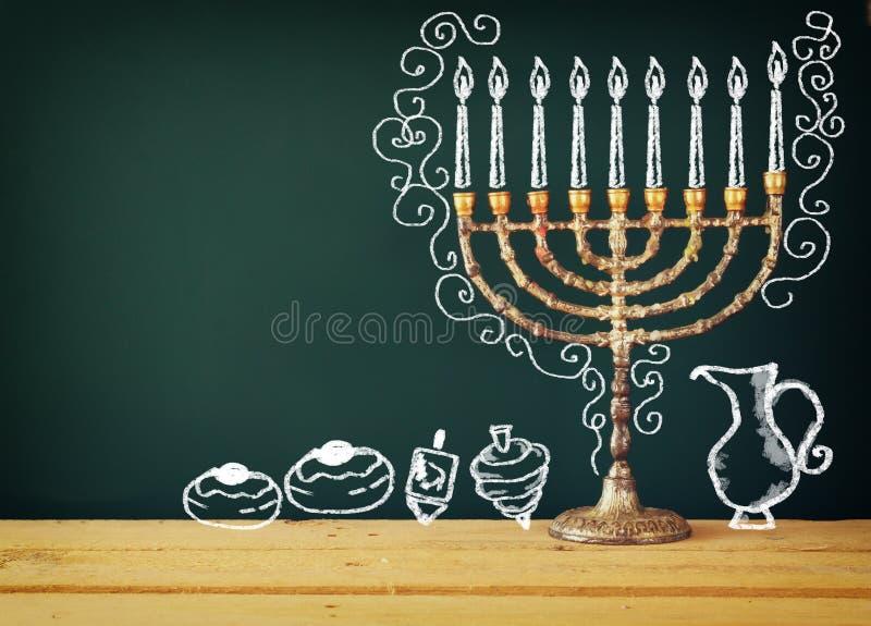 Beeld van Joodse vakantiechanoeka met tekenings menorah kaarsen (traditionele Kandelabers), donuts en dreidels (tol) over CH royalty-vrije stock fotografie