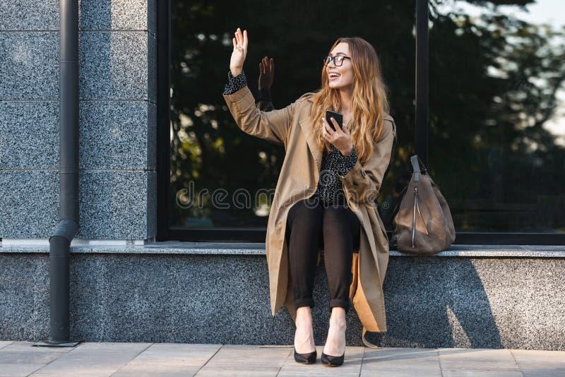 Beeld van joyous vrouw die mobiele telefoon met behulp van terwijl het zitten voor de bouw royalty-vrije stock foto