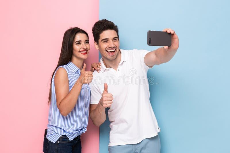 Beeld van Kaukasisch paar gebruikend mobiele telefoon en nemend selfie p royalty-vrije stock afbeelding