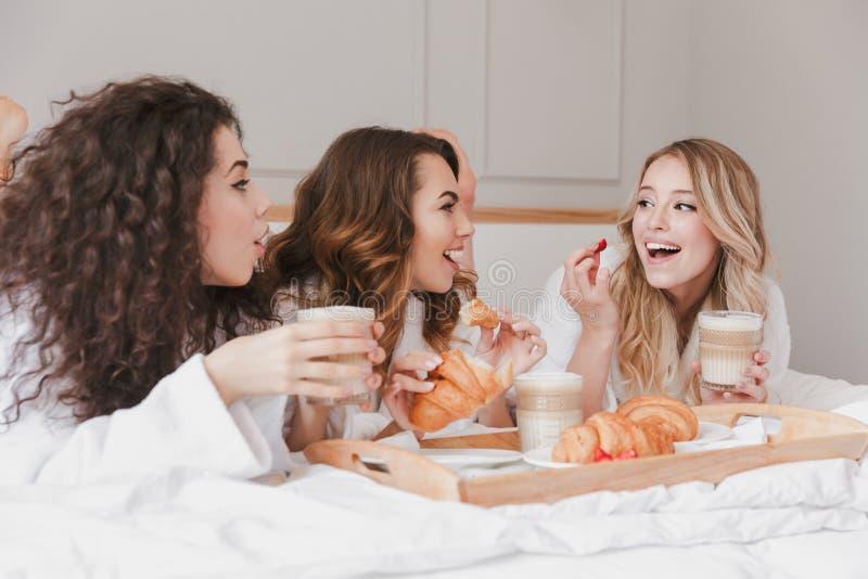 Beeld van Kaukasische het glimlachen vrouwenjaren '20 die witte ochtendjas dragen hav stock foto's