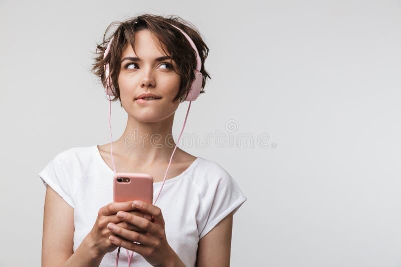 Beeld van Kaukasische vrouw in basissmartphone van de t-shirtholding terwijl het luisteren aan muziek met hoofdtelefoons royalty-vrije stock afbeeldingen