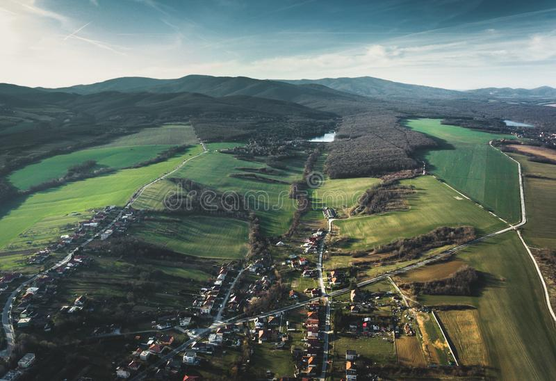 Beeld van klein dorp in Slowakije - Europa met twee grote meren en grote bergenheuvels op achtergrond Hilly Village met groen royalty-vrije stock foto's