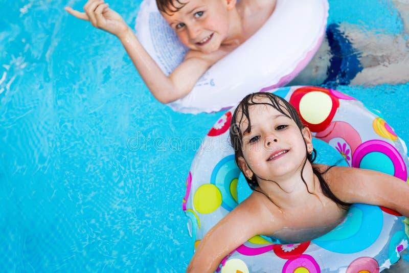 Beeld van kleine jonge geitjes die in zwembad genieten van royalty-vrije stock afbeelding
