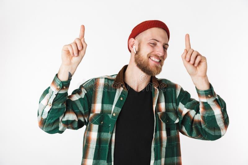 Beeld van knappe gebaarde kerel die hoed en plaidoverhemd dragen die, terwijl status geïsoleerd over witte achtergrond glimlachen stock afbeelding