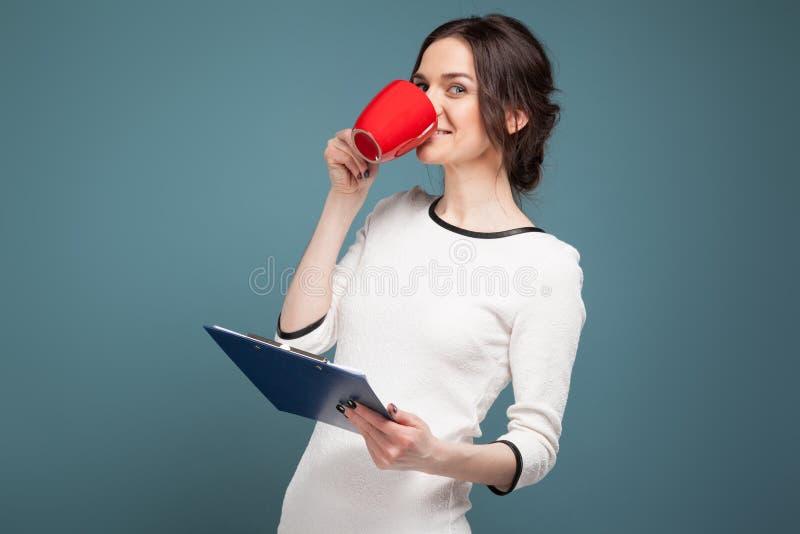 Beeld van knappe vrouw in lichte kleren die zich met coffe en opnamen in handen bevinden royalty-vrije stock afbeelding
