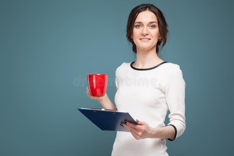 Beeld van knappe vrouw in lichte kleren die zich met coffe en opnamen in handen bevinden royalty-vrije stock foto's