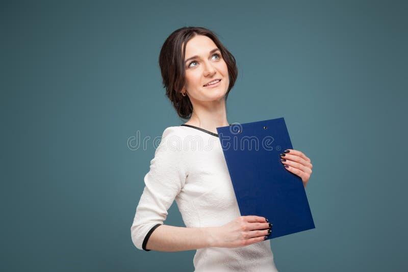 Beeld van knappe vrouw in lichte kleren die zich met opnamen in handen bevinden stock afbeeldingen