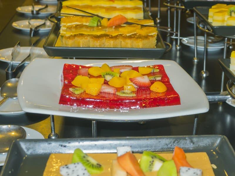 Beeld van koude rode geleicake met veel soort vruchten stock foto's