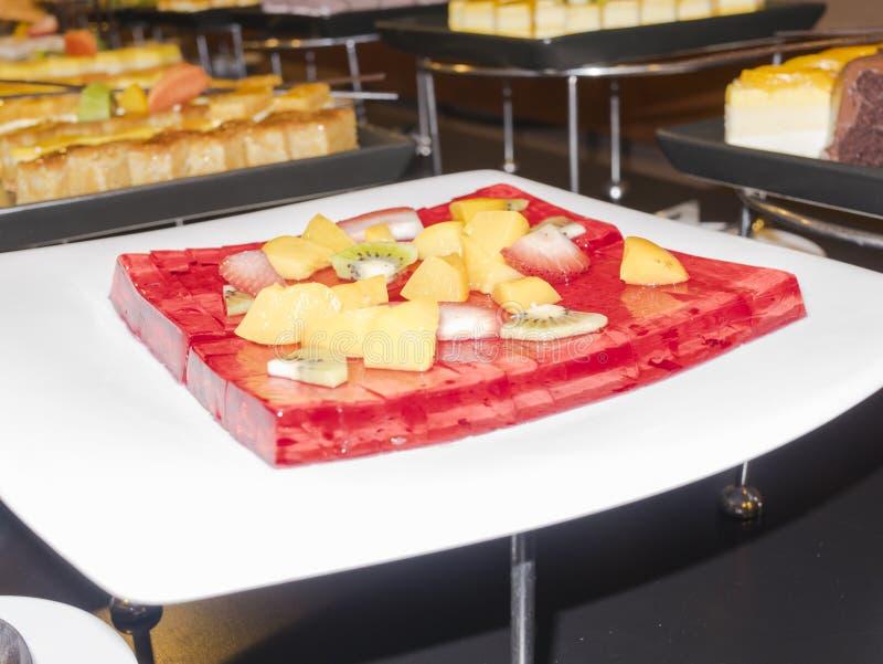 Beeld van koude rode geleicake met veel soort vruchten op buffet royalty-vrije stock fotografie