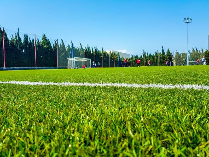Beeld van kunstmatig gras op de voorgrond en de achtergrond van kinderen die voetbal spelen stock foto
