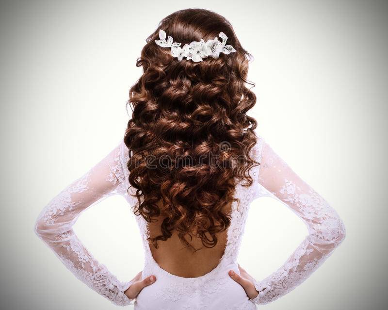 Beeld van lang krullend bruin haar donkerbruin meisje in witte huwelijkskleding met een low-cut rug stock afbeelding