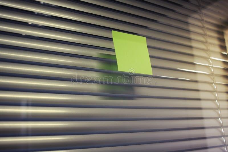 Beeld van lege kleverige nota over de muur van het bureauglas met jaloezie royalty-vrije stock foto