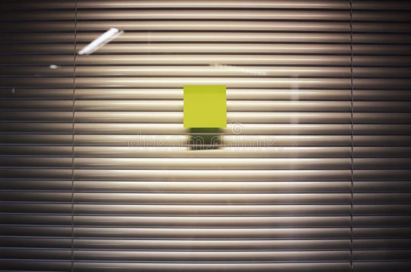 Beeld van lege kleverige nota over de muur van het bureauglas met jaloezie stock afbeeldingen