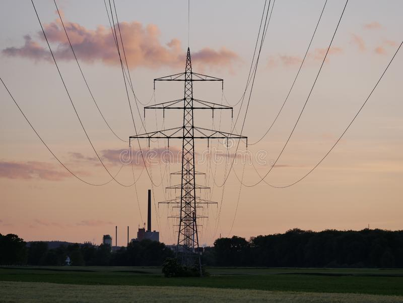 Beeld van machtslijn tijdens zonsondergang met elektrische centrale stock fotografie