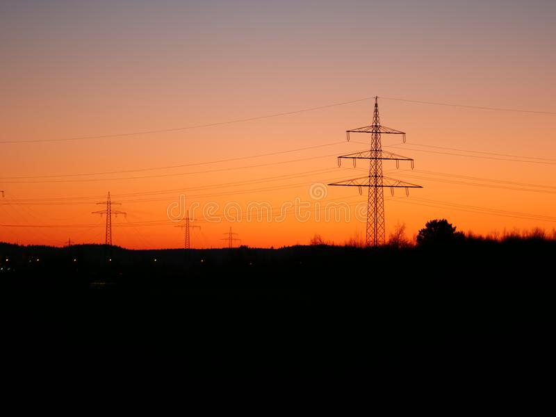 Beeld van machtspylonen in het landschap tijdens kleurrijke zonsondergang stock afbeeldingen