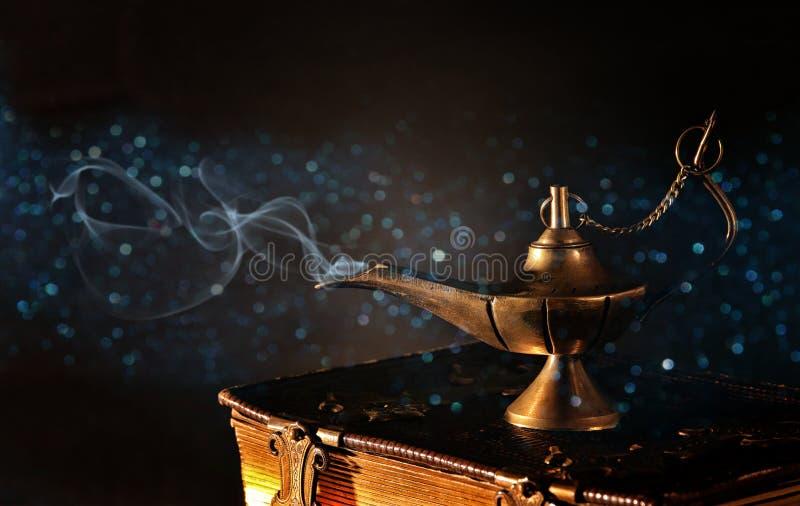 Beeld van magische aladdinlamp op oude boeken Lamp van wensen stock afbeeldingen