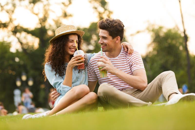 Beeld van man en vrouwenjaren '20 die op groen gras in park en het drinken dranken van plastic koppen zitten stock foto