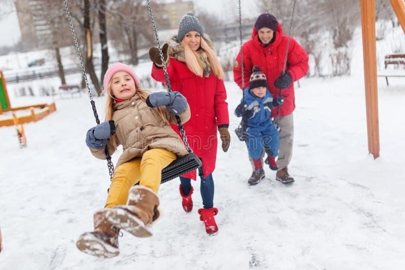 Beeld van meisje en jongen die in de winter in park met ouders slingeren royalty-vrije stock afbeeldingen