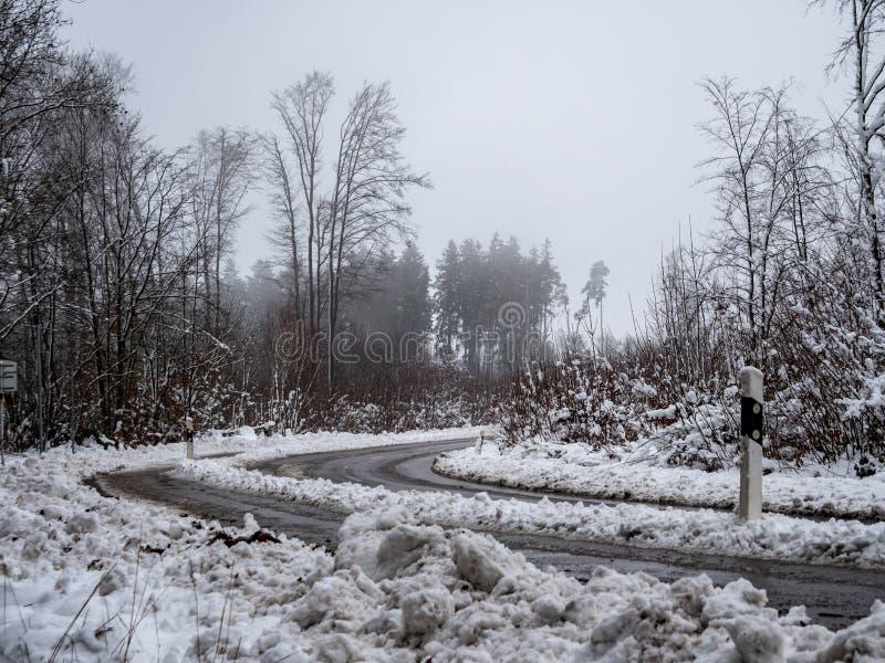 Beeld van mistige en sneeuw de winterweg royalty-vrije stock afbeelding