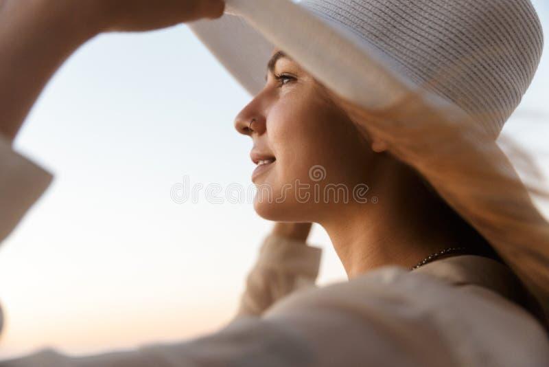 Beeld van modieuze vrouwenjaren '20 in de hoed die van het de zomerstro, terwijl het lopen door kust glimlachen stock afbeeldingen