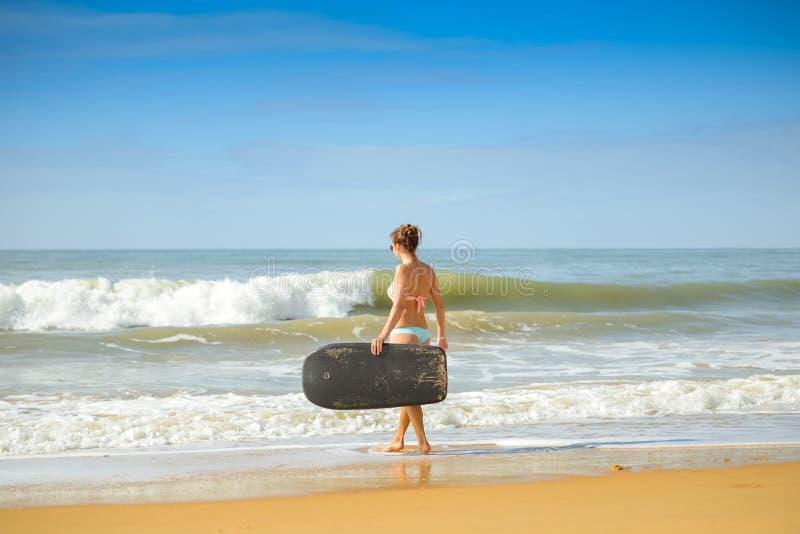 Beeld van mooi meisje met bodyboard, klaar voor pret De Zeeschelp van de kammossel op Roze royalty-vrije stock foto's