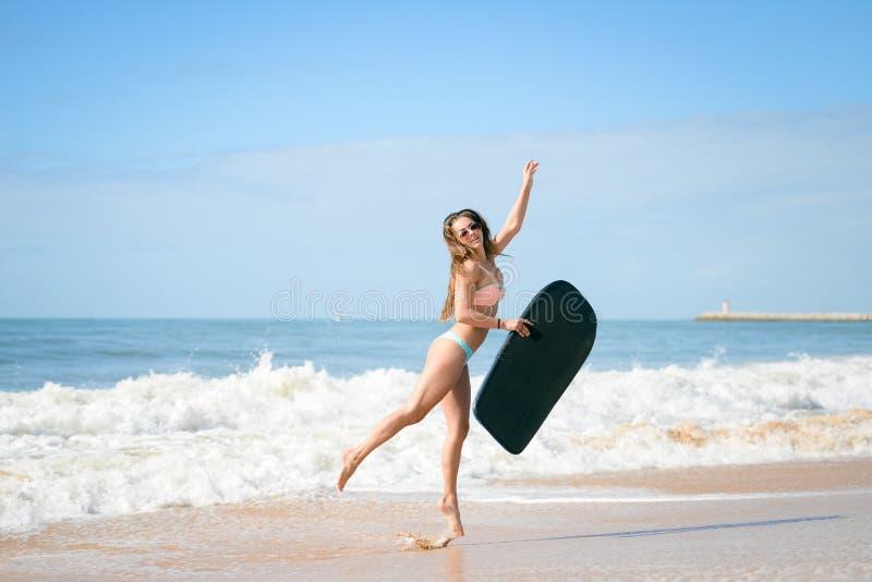 Beeld van mooi meisje met bodyboard, klaar voor pret De Zeeschelp van de kammossel op Roze royalty-vrije stock afbeeldingen