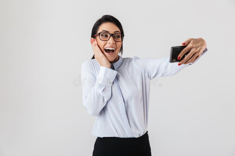 Beeld van mooie bureauvrouw die oogglazen dragen die selfie foto op celtelefoon nemen, dat over witte achtergrond wordt geïsoleer royalty-vrije stock fotografie