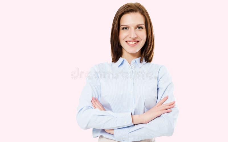 Beeld van mooie glimlach donkerbruine die vrouw status met wapens op roze achtergrond worden gekruist royalty-vrije stock afbeeldingen