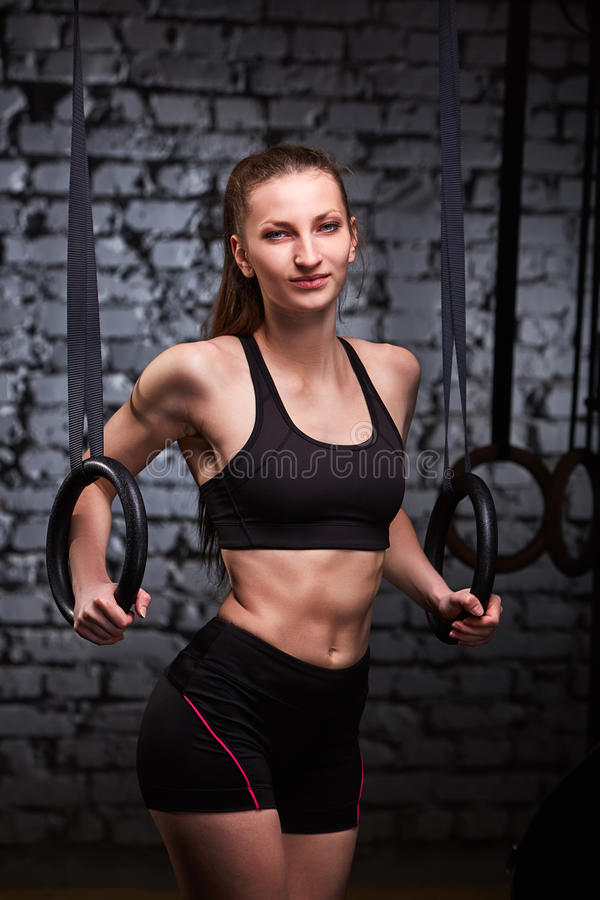 Beeld van mooie jonge sportieve vrouw in de zwarte sportwear het doen oefening trekkracht-UPS die gymnastiek- ringen gebruiken stock fotografie