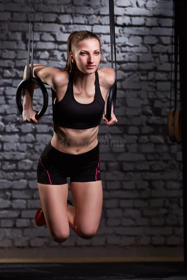 Beeld van mooie jonge sportieve vrouw in de zwarte sportwear het doen oefening trekkracht-UPS die gymnastiek- ringen gebruiken royalty-vrije stock afbeelding