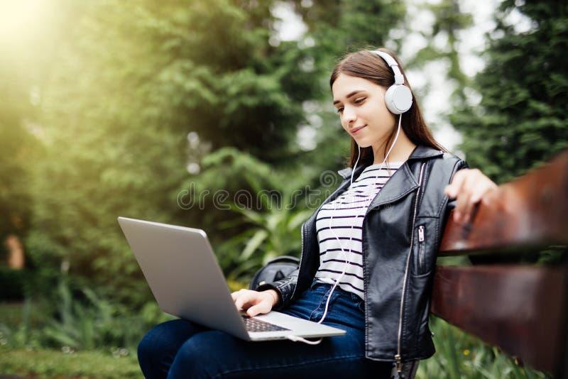 Beeld van mooie jonge vrouwenzitting in openlucht in park Het kijken opzij het luisteren muziek met hoofdtelefoons die laptop com royalty-vrije stock fotografie