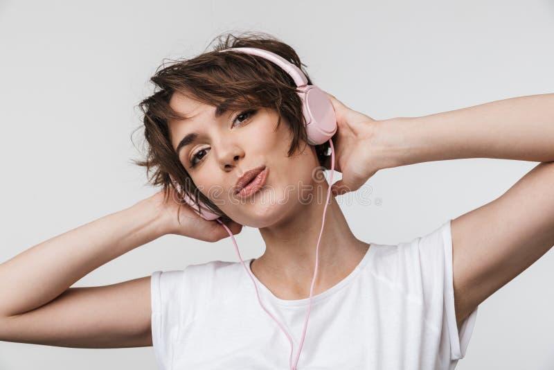 Beeld van mooie vrouw in basist-shirt die camera bekijken terwijl het luisteren aan muziek met hoofdtelefoons stock fotografie