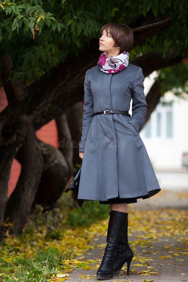 Beeld van mooie vrouw in grijze laag bij park royalty-vrije stock afbeelding