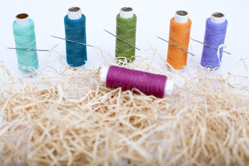 Beeld van multi Gekleurde naaiende draad met naald op het rafigras stock afbeelding