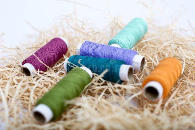 Beeld van multi Gekleurde naaiende draad op het rafigras stock afbeeldingen