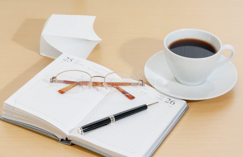 Beeld van ontwerper, de pen van de koffiekop en glazen stock fotografie