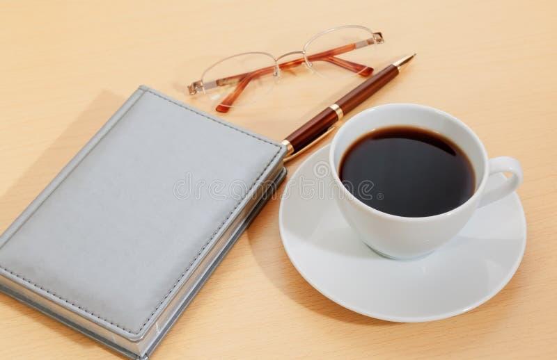 Beeld van ontwerper, koffiekop, pen en glazen Selectieve nadruk stock afbeeldingen