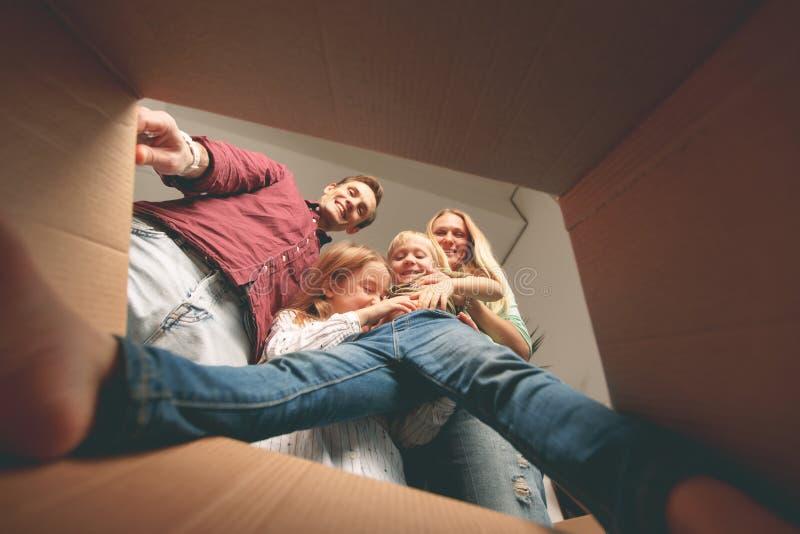 Beeld van ouders, dochter en zoon die binnenkartondoos kijken royalty-vrije stock fotografie