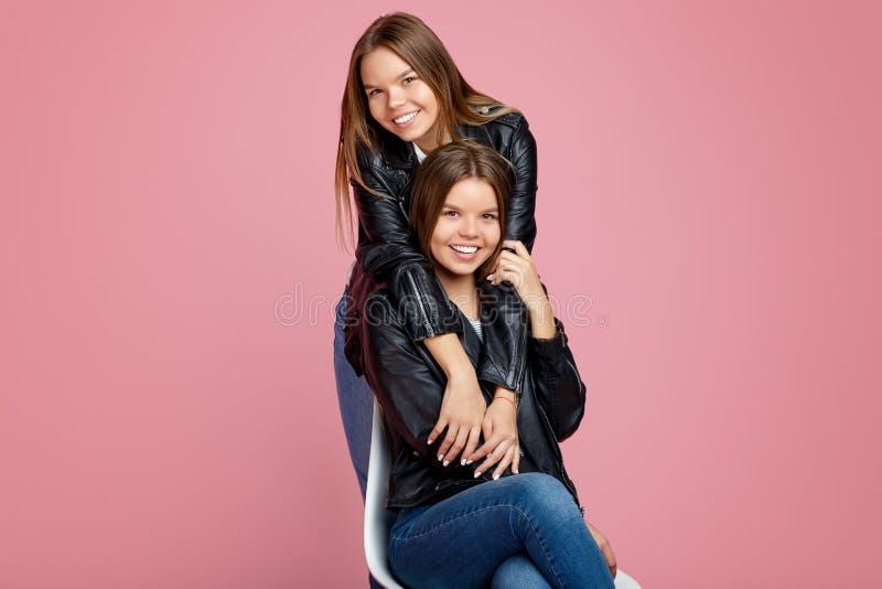 Beeld van over het charmeren van twee jonge tweelingzusters in leerjasjes met mooie glimlachomhelzing ich op roze achtergrond stock fotografie