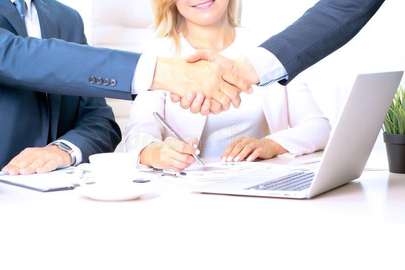 Beeld van partnershandenschudden over bedrijfsvoorwerpen op werkplaats royalty-vrije stock foto's