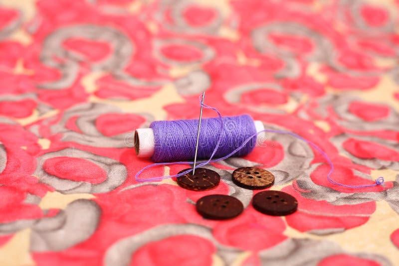 Beeld van purpere naaiende draad, naald en knoop vier stock fotografie