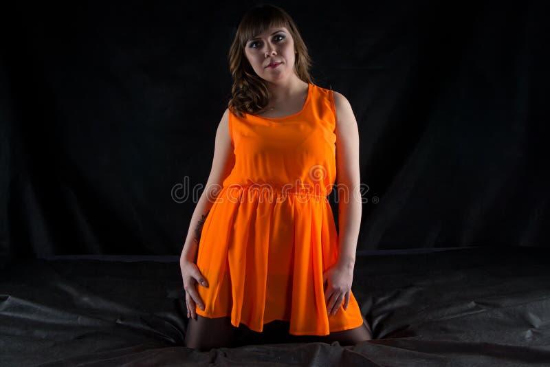 Beeld van ronde vrouw in oranje kleding stock foto's