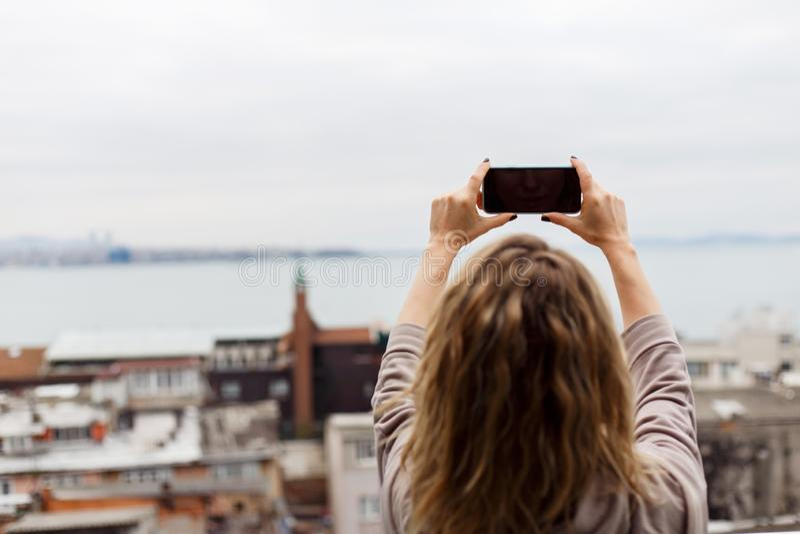 Beeld van rug die van krullend blonde beeld van zich nemen tegen vage achtergrond stock afbeelding