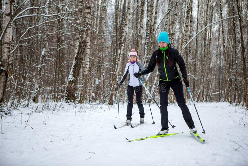 Beeld van sportenvrouwen en mannen die in de winterbos ski?en royalty-vrije stock afbeeldingen