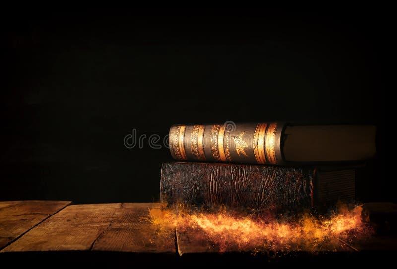 beeld van stapel antieke boeken over houten lijst en donkere achtergrond stock afbeeldingen