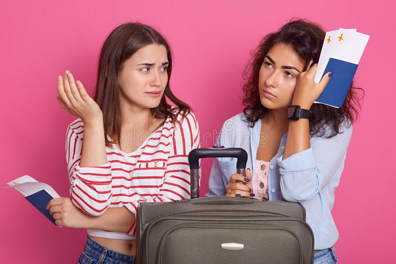 Beeld van toeristenmeisjes die op vlucht op vliegtuig wachten, zittend dichtbij koffer en het besteden tijd terwijl het spreken,  stock afbeelding