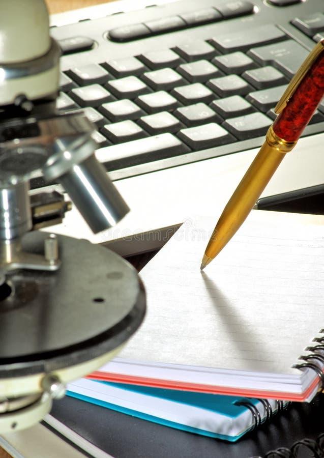 Beeld van toetsenbord, microscoop, notitieboekje en penclose-up stock foto