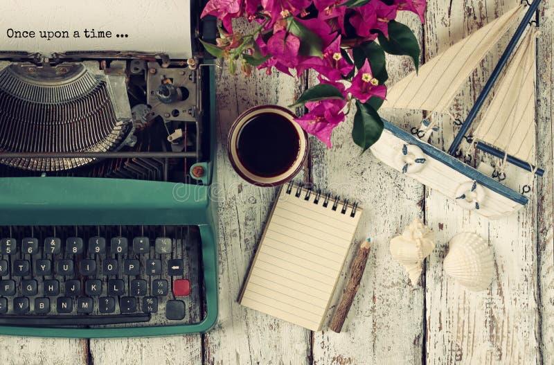Beeld van uitstekende schrijfmachine met uitdrukking eens, leeg notitieboekje, kop van koffie en oude zeilboot stock foto's