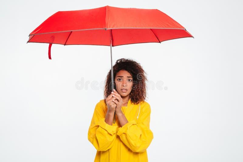 Beeld van verwarde Afrikaanse vrouw in regenjas het verbergen onder paraplu stock fotografie